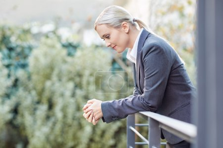 businesswoman leaning against railing of balcony