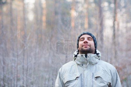 man breathing deeply in winter forest