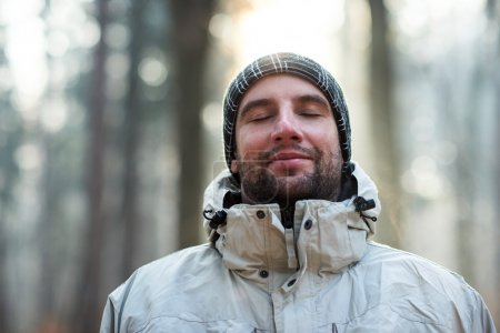 man standing in forest on cold day