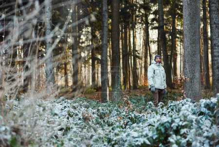 man in warm clothing standing in forest