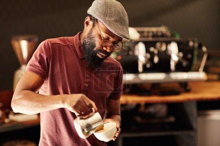 barista pouring milk into cappuccino