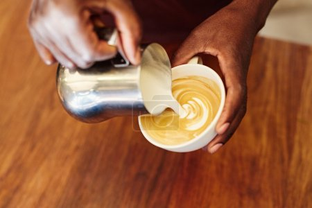 Photo pour Gros plan des mains d'un barista africain versant soigneusement du lait écumé à partir d'une cruche en acier inoxydable, dans une tasse à café pour former un motif chic sur un cappuccino - image libre de droit