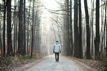 man walking away down road