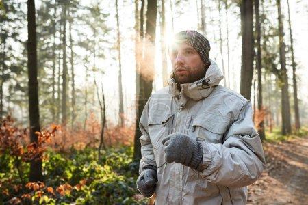 Man jogging in sunlit forest