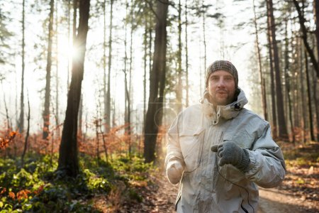 Man jogging in forest on cold morning