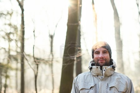 man with smile standing in winter forest