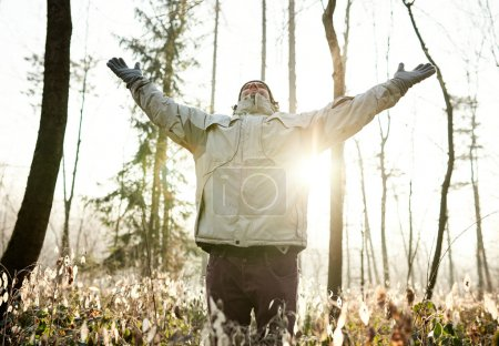 man standing in forest lifting arms up