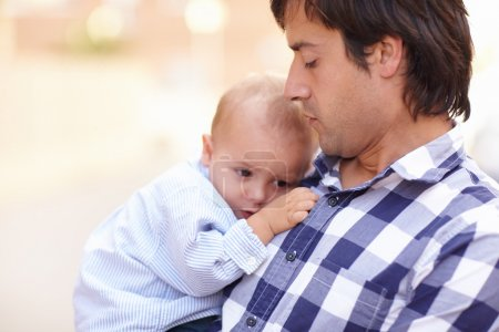 baby held safely to father chest