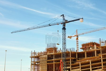 building under construction with cranes working