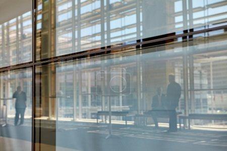 Photo pour Images abstraites de vrais hommes d'affaires en mouvement à travers le verre dans un centre de conférence animé - image libre de droit