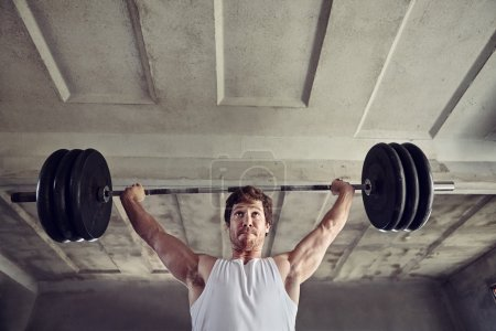 Photo for Low angle shot of a strong young man lifting heavy weights above his head with a determined expression - Royalty Free Image