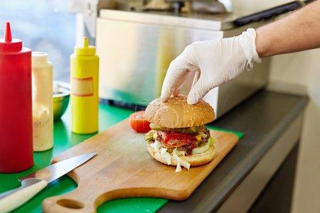Hand putting top bun on burger