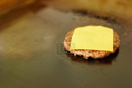 Hamburger patty frying on grill with cheese