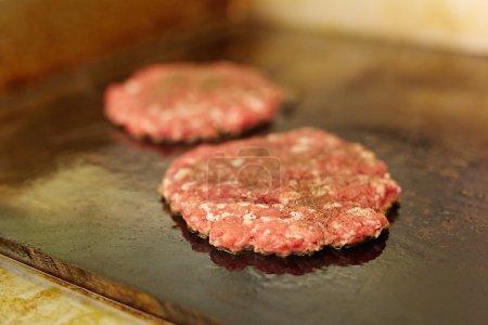 Frische Burger-Patties auf dem Grill braten