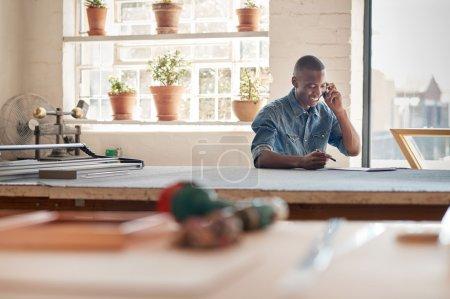 entrepreneur talking on phone in workshop