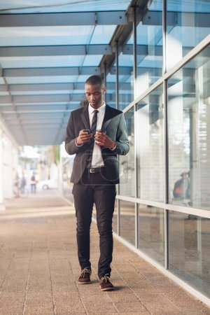 Businessman walking with phone and takeaway coffee