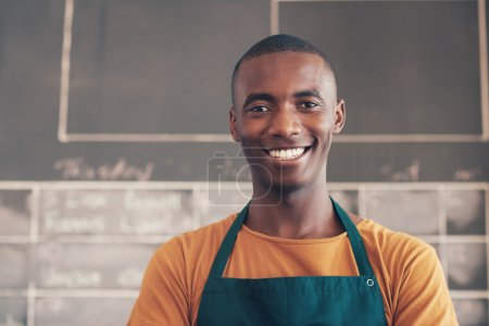 African craftsperson standing in workshop and smiling