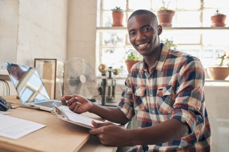 Entrepreneur holding paperwork at desktop