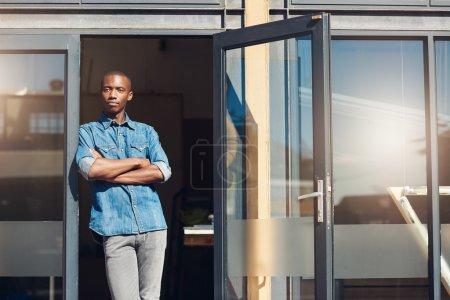 business owner standing in doorway of store