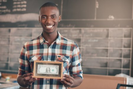 business owner holding framed dollar bill