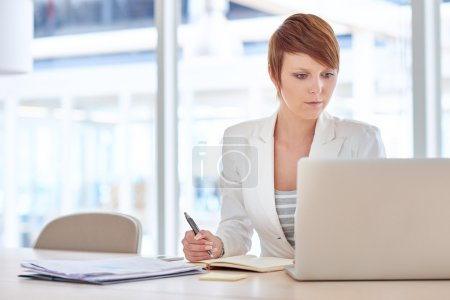 Businesswoman sitting at desk in lit office