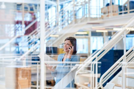 businesswoman reading report while talking on phone