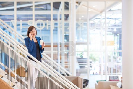 Businesswoman standing on stairs in bright office space