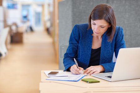 Businesswoman working on paperwork and writing notes