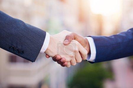 businessmen shaking hands together