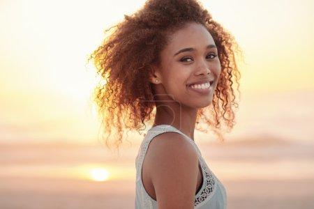 Foto de Retrato de una hermosa joven de pie en una playa al atardecer - Imagen libre de derechos
