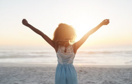 Photo for Beautiful young woman standing on a beach with her arms raised in the air - Royalty Free Image