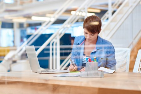 Photo for Young businesswoman is seen through the glass of an interior window, working at her desk in a modern office space, writing a note, with her laptop open in front of her - Royalty Free Image