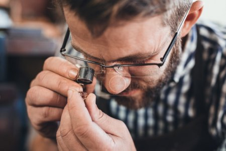 Photo for Closeup of a jeweler using a loupe to examine a gem he is working with while sitting at a bench in his workshop - Royalty Free Image