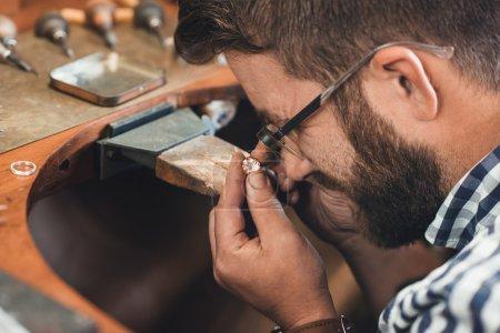 jeweler using loupe to examine gem