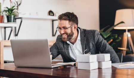 entrepreneur working on laptop while sitting at table