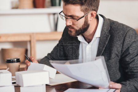 entrepreneur reading paperwork and preparing packages