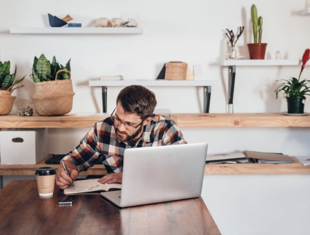 entrepreneur writing in notebook next to laptop