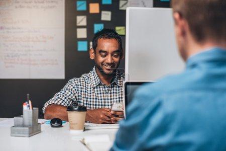 designer sitting at desk checking cellphone