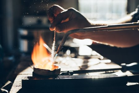 jeweler using torch to melt metal
