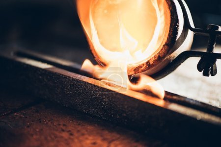 jeweler pouring molten metal from crucible