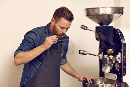owner smelling roasted coffee beans
