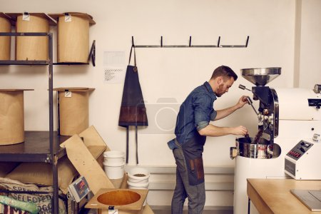 man working with roasting machine