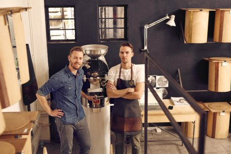 Photo for Portrait of two men in hipster style wear, smiling at the camera confidently in modern roast coffee beans workspace with neat storage containers - Royalty Free Image