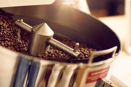 Photo pour Café aromatique en grains fraîchement torréfié dans un appareil moderne brillant et neuf avec des pièces métalliques propres dans un roastère - image libre de droit