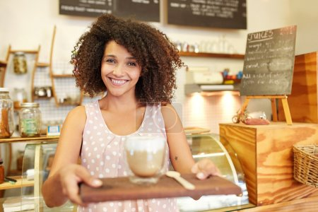 Photo for Focus on the foreground of young mixed race waitress holding wooden tray with Latte - Royalty Free Image