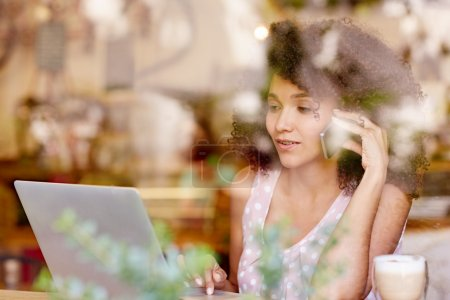 Woman typing on laptop and talking on phone