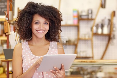 Photo for Portrait of a beautiful young woman with an afro hairstyle smiling at the camera while using digital tablet in her coffee shop - Royalty Free Image