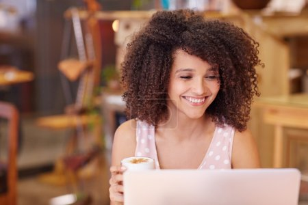 Woman in coffee shop using laptop