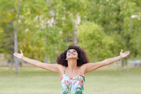 woman standing in park with stretching arms
