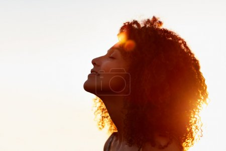 Photo for Profile portrait of a beautiful woman with afro style hair silhouette against golden sun flare on a summer evening - Royalty Free Image